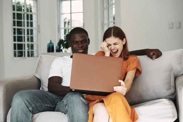 Homem e mulher na sala de estar no sofá em frente a um laptop assistindo filmes