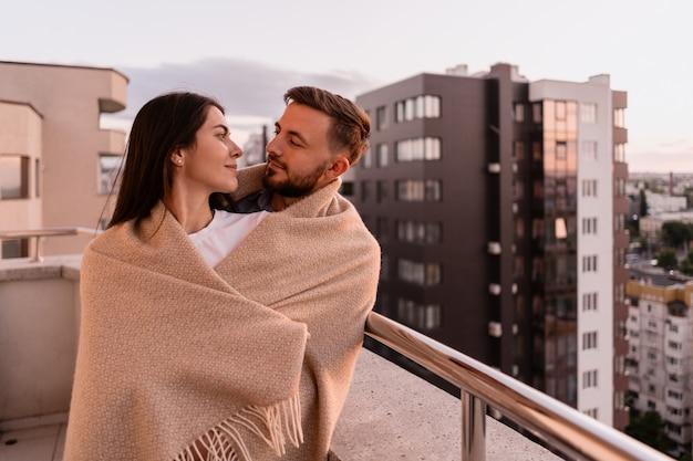 Homem e mulher na varanda ao pôr do sol na cidade