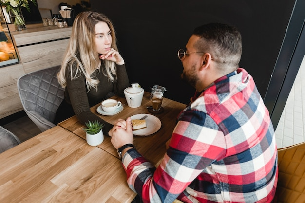 Homem e mulher namorando no café. garoto e garota felizes. casal apaixonado sentado em casa se comunicando