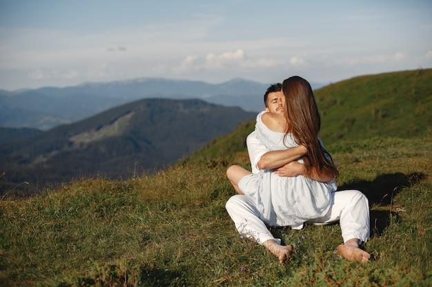 Homem e mulher nas montanhas. jovem casal apaixonado ao pôr do sol. mulher de vestido azul.
