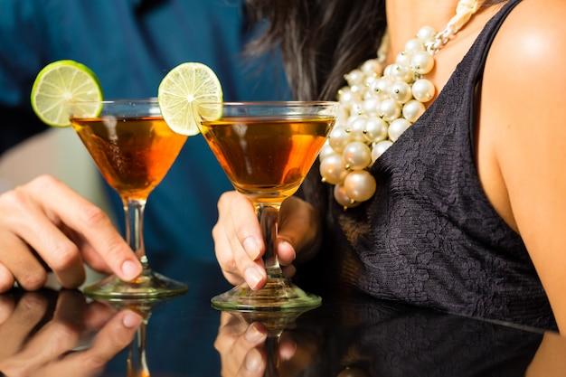 Homem e mulher no bar com cocktails