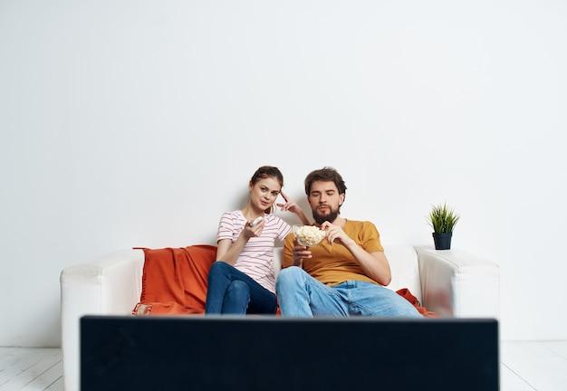 Homem e mulher no sofá assistindo a um filme de entretenimento doméstico