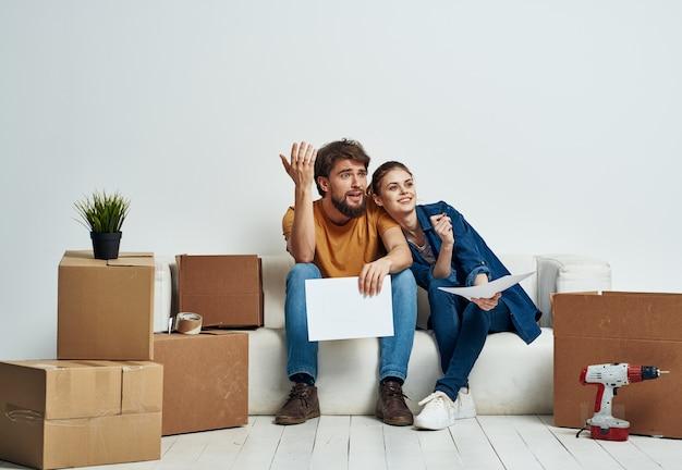 Homem e mulher no sofá branco interior caixas de papelão estilo de vida.