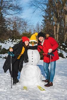 Homem e mulher, novo esquiador, boneco de neve, atividades de inverno