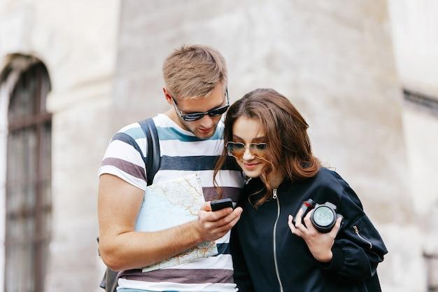Homem e mulher observam algo no telefone em pé com mapa turístico