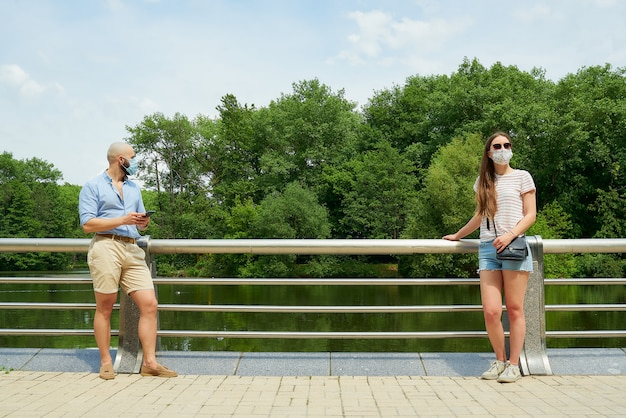 Homem e mulher olhando em direções diferentes, mantendo distância alguns metros para evitar a propagação de coronavírus perto do rio.
