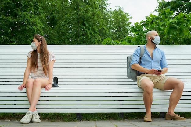 Homem e mulher olhando em direções diferentes, sentados em extremos opostos de um banco, mantendo distância um do outro para evitar a propagação do coronavírus.