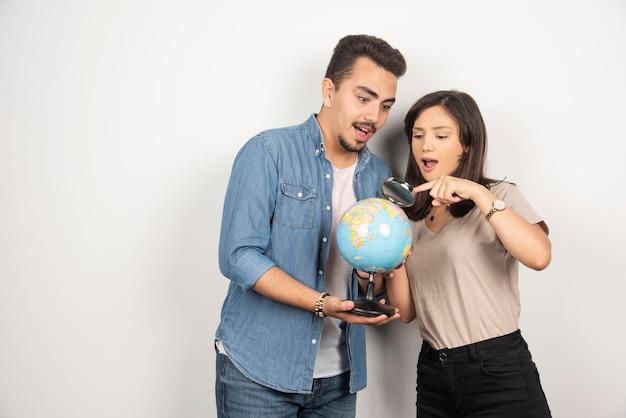 Homem e mulher olhando na globo em branco.