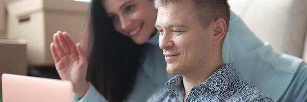Homem e mulher olhando para a tela do laptop e acenando com a mão