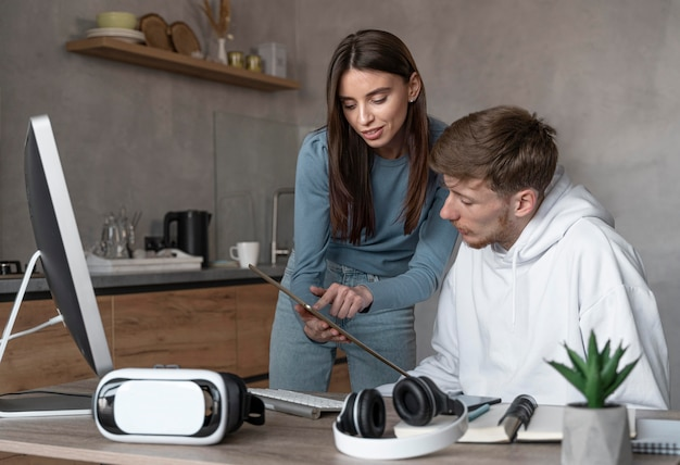 Homem e mulher olhando para um tablet juntos no trabalho