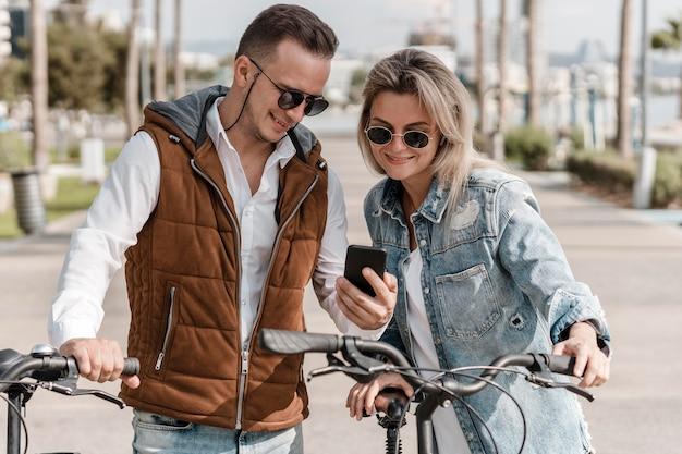 Homem e mulher olhando para um telefone ao lado de suas bicicletas