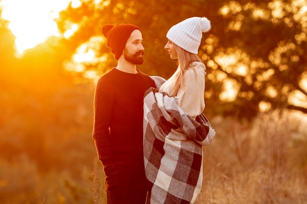 Homem e mulher olhando um ao outro ao pôr do sol
