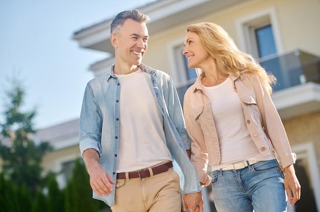 Homem e mulher olhando um para o outro de mãos dadas