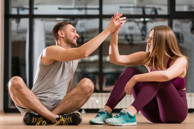 Homem e mulher orgulhosos de seus exercícios
