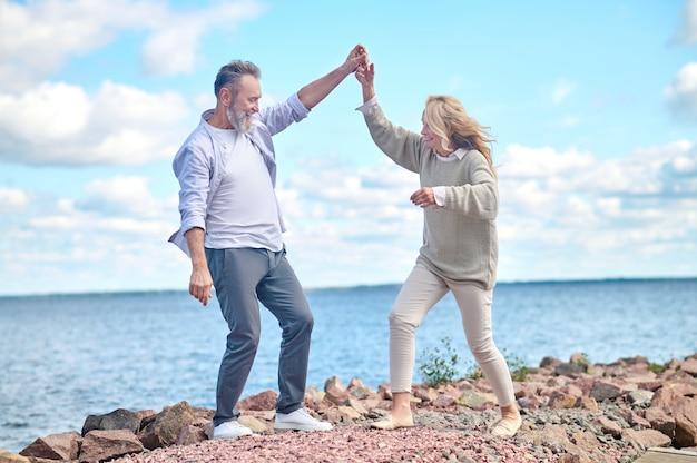 Homem e mulher otimistas caminhando perto do mar