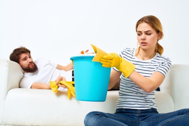Homem e mulher perto do sofá limpeza materiais prestação de serviços
