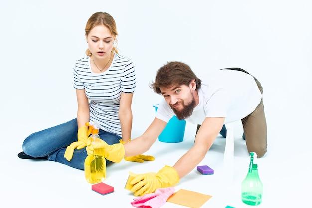 Homem e mulher perto dos trapos de detergente do sofá esponjas luvas protetoras. foto de alta qualidade