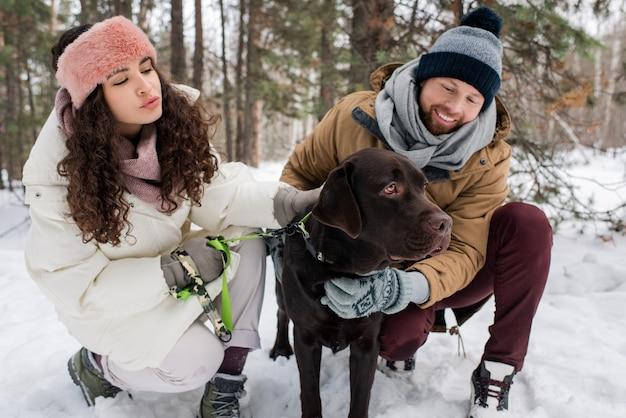 Homem e mulher petting dog
