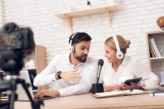 Homem e mulher podcasters posando na câmera para podcast de rádio.
