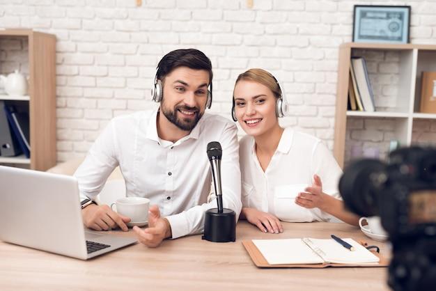 Homem e mulher podcasters se entrevistam.