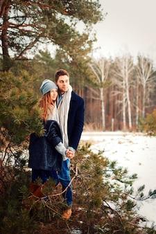 Homem e mulher posando ao lado de um pinheiro em um dia de inverno