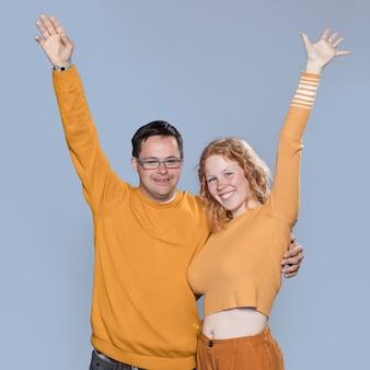 Homem e mulher posando com as mãos para cima