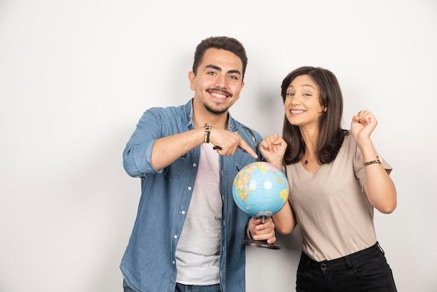 Homem e mulher posando com globo em branco.