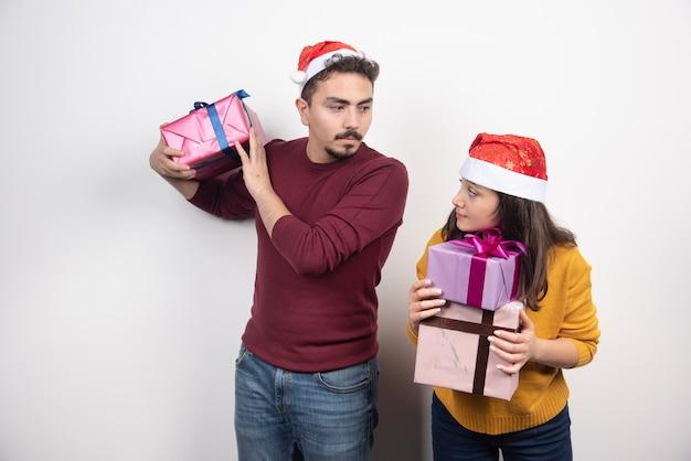 Homem e mulher posando com presentes de natal.