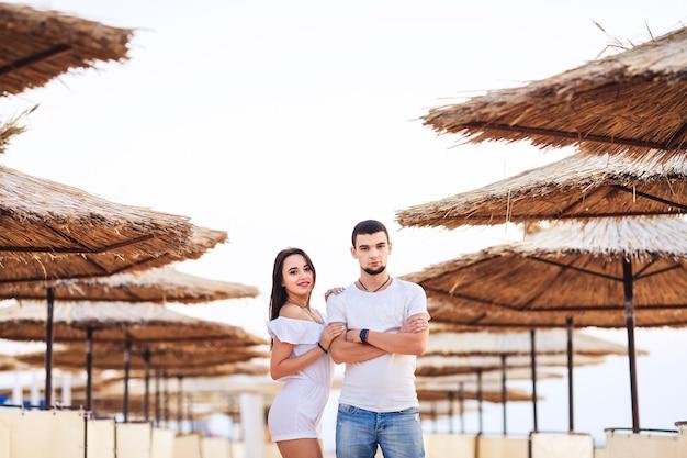 Homem e mulher posando na praia entre guarda-chuvas de junco. o conceito de férias de verão no mar.