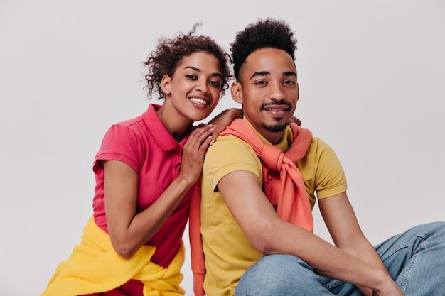 Homem e mulher positivos olhando com um sorriso para a câmera na parede isolada