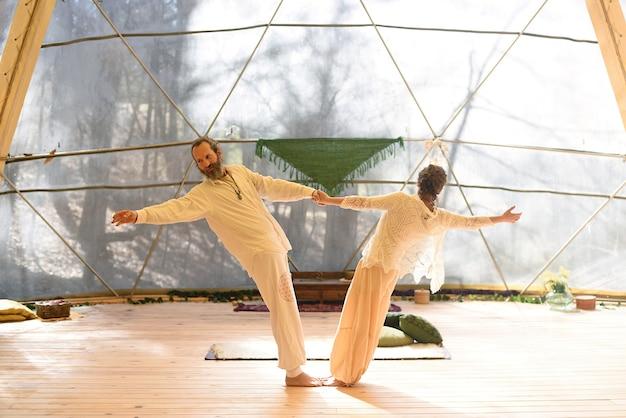 Homem e mulher praticando ioga tantra em postura de equilíbrio