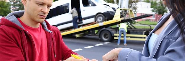 Homem e mulher preenchem papelada após acidente de carro. conceito de agente de seguros