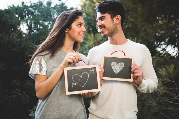 Homem e mulher que prendem dois quadros com corações desenhados