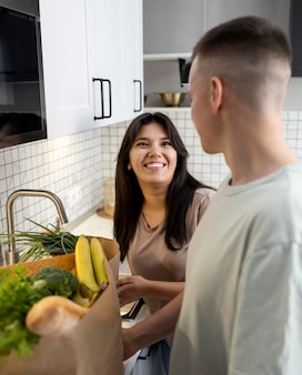 Homem e mulher recebendo sacolas de papel de supermercado após fazerem compras online