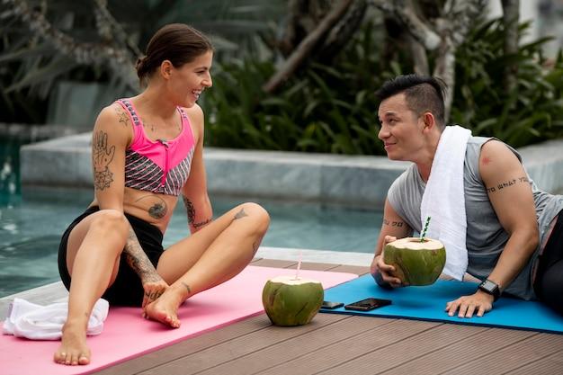 Homem e mulher relaxam depois da ioga com água de coco