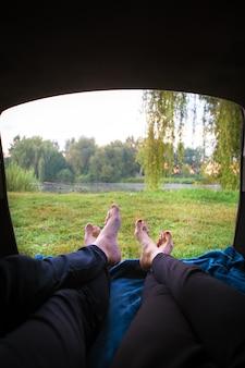 Homem e mulher relaxando no porta-malas de um carro perto de um lago