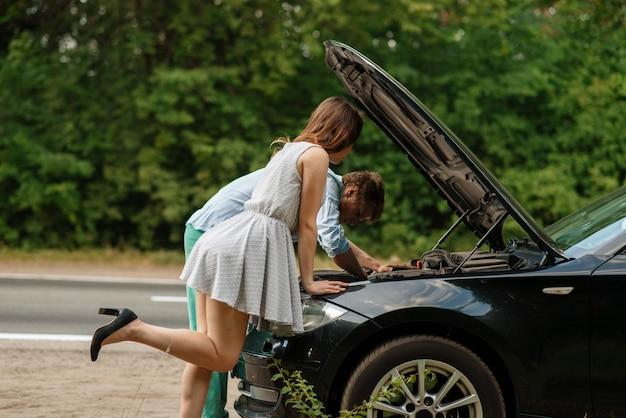 Homem e mulher reparam automóvel na estrada, avaria do carro.