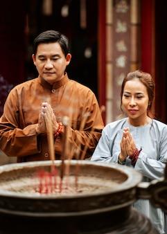 Homem e mulher rezando no templo com incenso