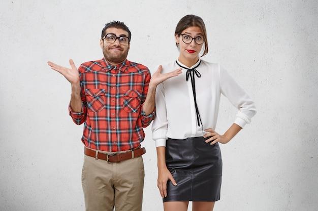 Homem e mulher ridículos vestidos formalmente, usam óculos, encolhem os ombros em perplexidade
