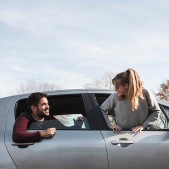 Homem e mulher saindo da janela do carro