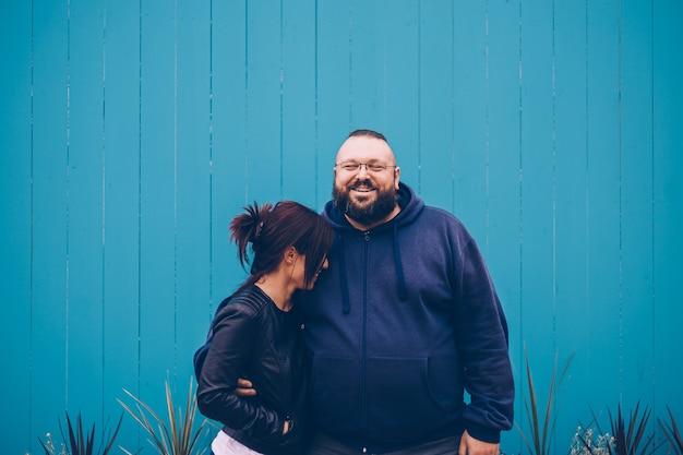Homem e mulher se abraçando e sorrindo alegremente