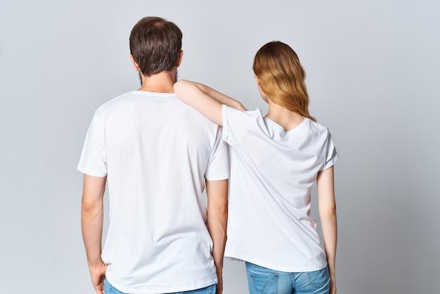 Homem e mulher se abraçando em uma maquete de camiseta branca vista traseira