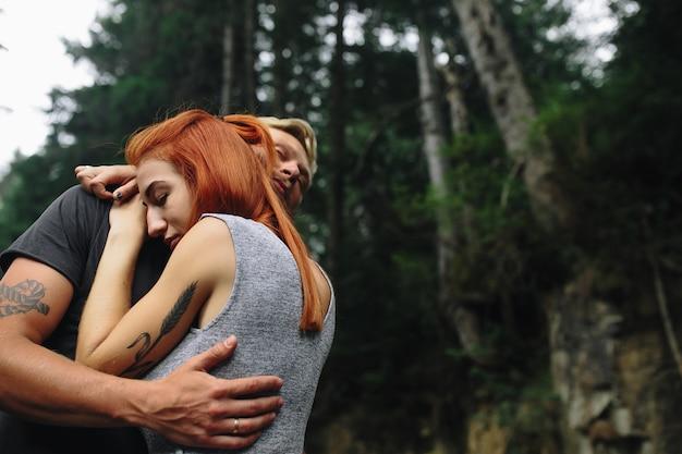 Homem e mulher se abraçando ternamente na natureza