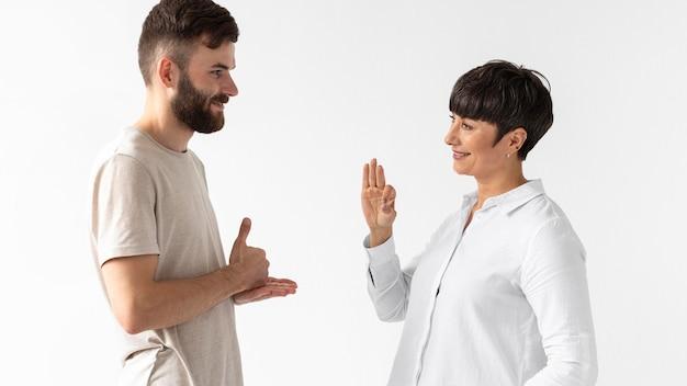 Homem e mulher se comunicando através da linguagem de sinais