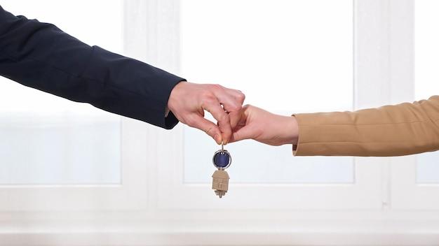 Homem e mulher se cumprimentam entregando as chaves do apartamento