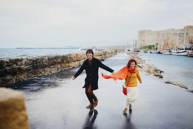 Homem e mulher se divertem na chuva, costa vazia