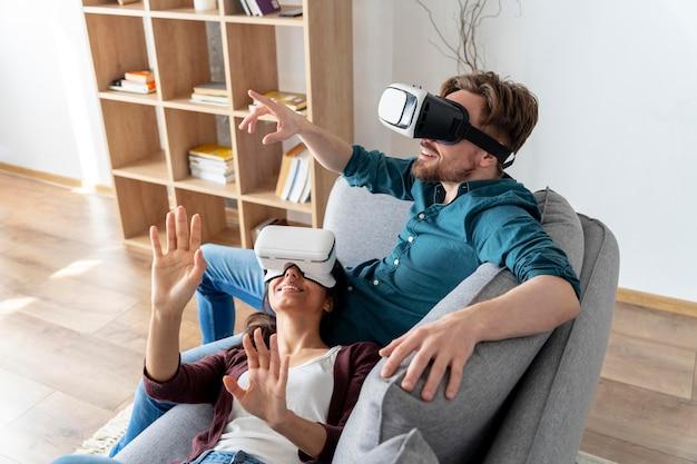 Homem e mulher se divertindo em casa com fone de ouvido de realidade virtual