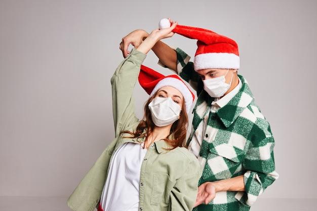 Homem e mulher se divertindo juntos com máscaras médicas, feriado de natal