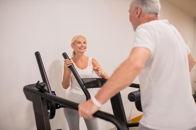 Homem e mulher se exercitando em esteiras e se sentindo bem
