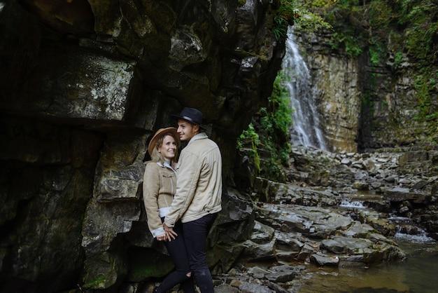 Homem e mulher se levantam e se abraçam nas rochas, perto de árvore, floresta e lago. paisagem de uma antiga pedreira de granito industrial. canyon.